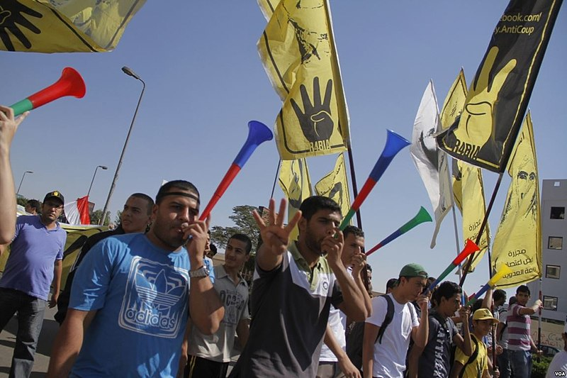 800px-Anti-coup_protesters_with_R4bia_sign_in_Nasr_City-Cairo_11-Oct-2013