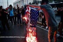 عکس/ یونانی ها پرچم آمریکا را به آتش کشیدند